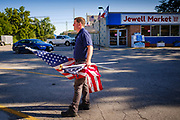 "03 AUGUST 2020 - JEWELL, IOWA:  A vendor holds American flags in front of the Jewell Market. The only grocery store in Jewell, a small community in central Iowa, closed in 2019. It served four communities within a 20 mile radius of Jewell. Some of the town's residents created a cooperative to reopen the store. They sold shares to the co-op and  held fundraisers through the spring. Organizers raised about $225,000 and bought the store, which had its ""soft opening"" July 8. The store celebrated its official reopening Monday August 3. Before the reopening, Jewell had been a ""food desert"" for seven months. The USDA defines rural food deserts as having at least 500 people in a census tract living 10 miles from a large grocery store or supermarket. There is a convenience store in Jewell, but it sells mostly heavily processed, unhealthy snack foods that are high in fat, sugar, and salt.            PHOTO BY JACK KURTZ"
