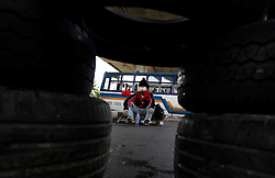 An anti-government protester is seen from between tires used as blockades as they prepare to face-off the Thai army during pitched battles on the streets of Bangkok, Thailand, 13 April 2009. Thai Prime Minister Abhisit Vejjajiva declared a state of emergency in Bangkok to quell anti-government protests that forced the cancellation of the ASEAN summit in Pattaya. Thai soldiers fired shots at protestors driving buses at them and used tear gas against demonstrators blocking a main road junction in Bangkok in a major escalation of political violence in the kingdom