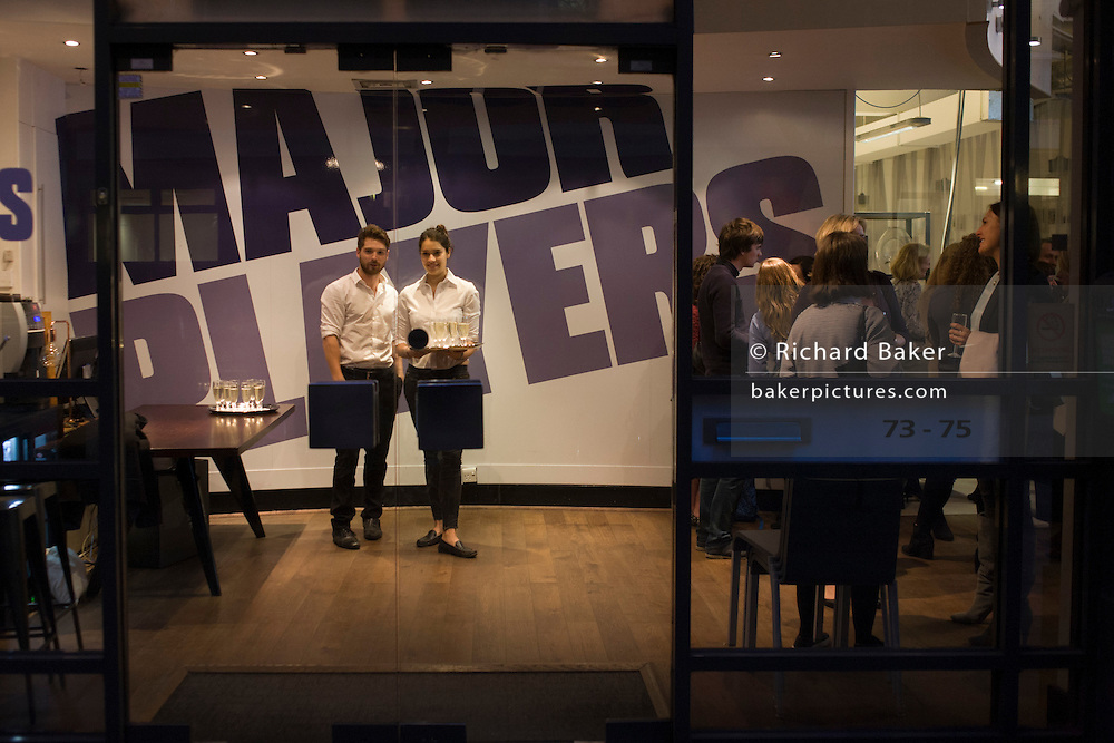 Waiters await guests at the entrance of a business in central London.