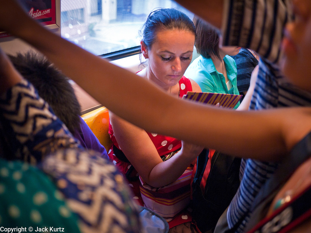 02 JULY 2011 - BANGKOK, THAILAND:   A woman reads a Thai travel guidebook while riding the Sukhumvit line of the Bangkok Sky Train. The Bangkok Mass Transit System, commonly known as the BTS Skytrain, is an elevated rapid transit system in Bangkok, Thailand. It is operated by Bangkok Mass Transit System Public Company Limited (BTSC) under a concession granted by the Bangkok Metropolitan Administration (BMA). The system consists of twenty-three stations along two lines: the Sukhumvit line running northwards and eastwards, terminating at Mo Chit and On Nut respectively, and the Silom line which plies Silom and Sathon Roads, the Central Business District of Bangkok, terminating at the National Stadium and Wongwian Yai. The lines interchange at Siam Station and have a combined route distance of 55 km.    PHOTO BY JACK KURTZ