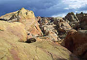 Mammatus clouds bulge beneath cumulonimbus clouds over yellow and red sandstone on the White Domes trail in Valley of Fire State Park,  Nevada, USA. Starting more than 150 million years ago, great shifting sand dunes during the age of dinosaurs were compressed, uplifting, faulted, and eroded to form the park's fiery red sandstone formations. The park also boasts fascinating patterns in limestone, shale, and conglomerate rock. The park adjoins Lake Mead National Recreation Area at the Virgin River confluence, at an elevation of 2000 to 2600 feet (610-790 m), 50 miles (80 km) northeast of Las Vegas, USA. Park entry from Interstate 15 passes through the Moapa Indian Reservation.