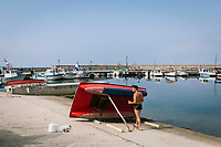 """PISCIOTTA, ITALY - 22 APRIL 2018: A man paints a pedal boat in the harbour of Pisciotta, Italy, on April 22nd 2018.<br /> <br /> Former restaurant owners Donatella Marino and her husband Vittorio Rimbaldo have spent the recent years preparing and selling salted anchovies, called alici di menaica, to a growing market thanks to a boost in visibility from the non-profit Slow Food.  The ancient Menaica technique is named after the nets they use brought by the Greeks wherever they settled in the Mediterranean. Their process epitomizes the concept of slow food, and involves a nightly excursion with the special, loose nets that are built to catch only the larger swimmers. The fresh, red anchovies are immediately cleaned and brined seaside, then placed in terracotta pots in between layers of salt, to rest for three months before they're aged to perfection.While modern law requires them to use PVC containers for preserving, the government recently granted them permission to use up to 10 chestnut wood barrels for salting in the traditional manner. The barrels are """"washed"""" in the sea for 2-3 days before they're packed with anchovies and sea salt and set aside to cure for 90 days. The alici are then sold in round terracotta containers, evoking the traditional vessels that families once used to preserve their personal supply.<br /> <br /> Unlike conventional nets with holes of about one centimeter, the menaica, with holes of about one and half centimeters, lets smaller anchovies easily swim through. The point may be to concentrate on bigger specimens, but the net also prevents overfishing."""