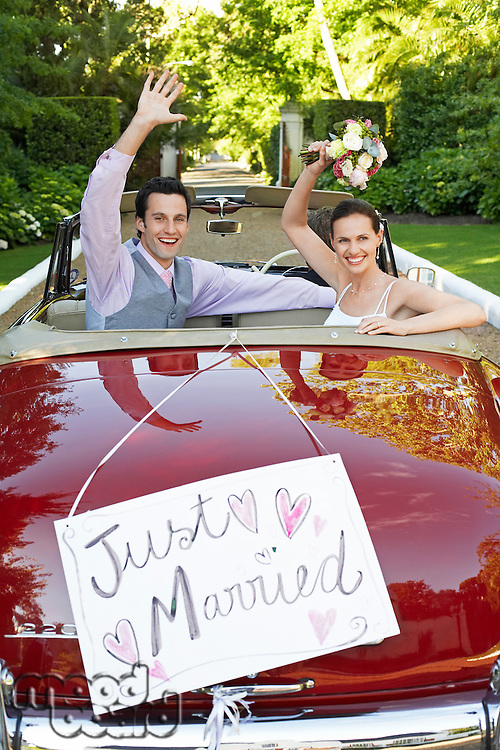 Mid adult bride and groom in retro car waving hands