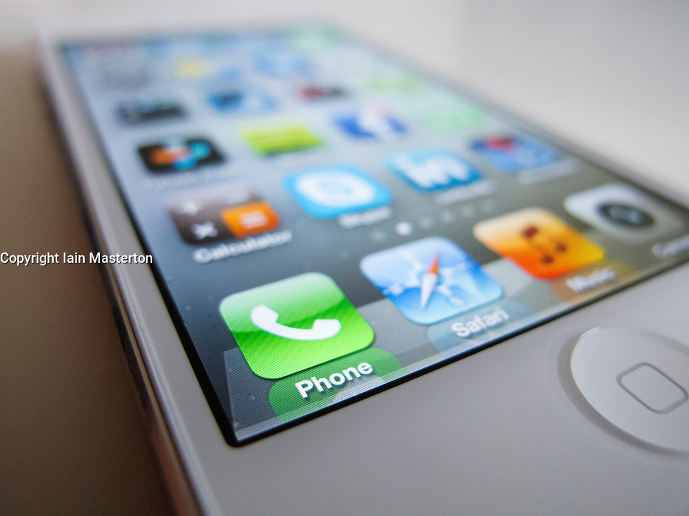 Close-up of new iPhone 5 smart phone showing screen with many apps