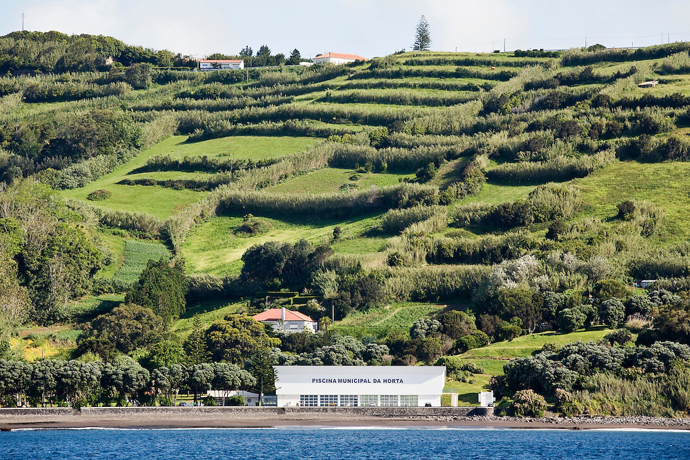 The municipal swimming pool of Horta on the beach backed by green hills, typical of The harbor of Horta on the island of Faial. One of of the Azores,  a group of islands in the Atlantic that are a part of Portugal and the European Union.