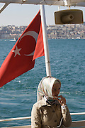 Istanbul. Ferry on the Bosporus, European side in the background. Young woman with traditional headdress.