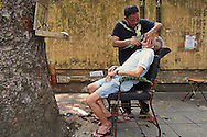 A street barber shaves a client in a street of Hanoi, Vietnam, Southeast Asia, 2016