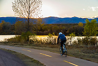 Man bicycling at sunset on the extensive bike trails in Littleton, Colorado USA.