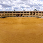 The Plaza de toros de Ronda, the oldest bullfighting ring in Spain. It was built in 1784 in the Neoclassical style by the architect José Martin de Aldehuela, The arena has a diameter of 66 metres (217 ft), surrounded by a passage formed by two rings of stone. There are two layers of seating, each with five raised rows and 136 pillars that make up 68 arches.