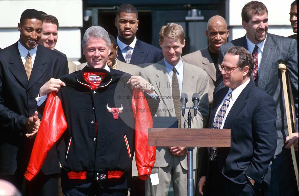 President Bill Clinton shows off his Chicago Bulls jacket gifted him by Bulls Chairman Jerry Reinsdorf as star Scottie Pippen looks on during an event on the South Lawn of the White House April 3, 1997. The event honored the NBA Champion Chicago Bulls.
