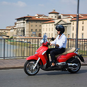 Man riding Aprilia Scarabeo scooter across Ponte allle Grazie with Ponte Vecchio in distance, Firenze, Italy<br />