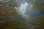 Nederland, Overijssel, Gemeente Steenwijkerland, 08-09-2009. Nationaal Park De Weerribben. Het landschap is het resultaat van het winnen van turf, na het steken van de turf (waardoor de 'trekgaten' ontstonden) werd dit te drogen gelegd op legakkers (de 'ribben'). Tegenwoordig vindt er rietteelt plaats (dekriet), de rook is het gevolg van het branden van rietvelden. Het gecontroleerd branden van rietvelden wordt toegepast om het riet wat door intensief maaien (door rietdekbedrijven) verruigd is en door ziekte is aangetast, weer nieuw leven in te blazen. .The National Park Weerribben. The landscape is the result of the extraction of peat, after digging the peat (creating  the 'pull holes'), it was to layed to dry on fields (the 'ribs'). Today production of reed takes place (thatching), the smoke was caused by burning cane fields.The controlled burning of the reed  fields  to renew the reed.toeslag); aerial photo (additional fee required); .foto Siebe Swart / photo Siebe Swart