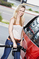 Young Woman Filling Up at the Gas Station