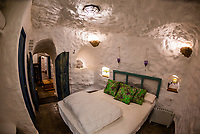 Interior view of bedroom,  Balcones de Piedad, Los Balcones, near Guadix, Granada Province, Andalusia, Spain. Five cave apartments in this boutique hotel give visitors the opportunity to stay in a luxury suite built into a cave.