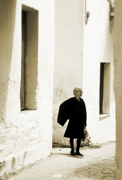 Old woman standing in alleyway on the island of Mykonos, Greece.
