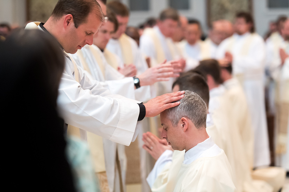 DENVER, CO - MAY 13: Peter Wojda prays as priests lay their hands upon him during his ordination to the priesthood at the Cathedral Basilica of the Immaculate Conception on May 13, 2017, in Denver, Colorado. (Photo by Daniel Petty/for Denver Catholic)
