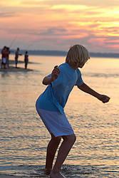 young boy at the water's edge skimming rocks in East Hampton,NY