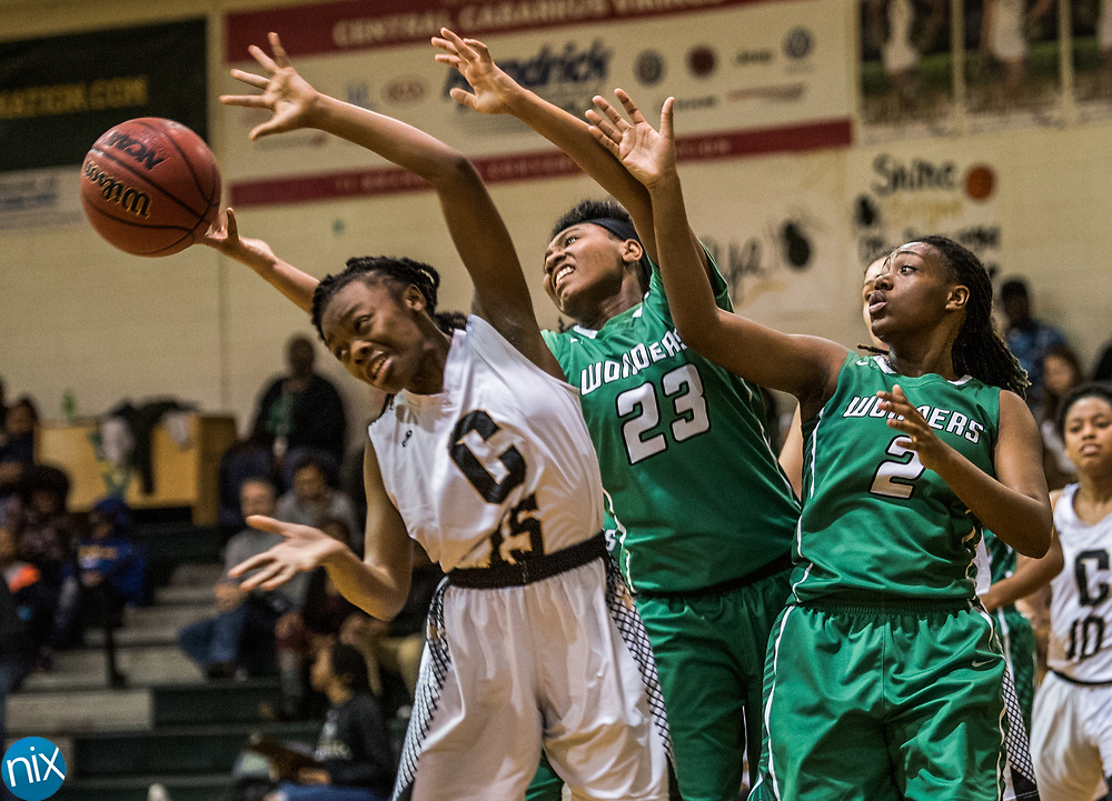 Concord's Janaya Miller (15) and Kannapolis' Jaliyah Simmons (23) and Debrisha Campbell (2) fight for a loose ball during a South Piedmont Conference basketball game Saturday night at Central Cabarrus High School.