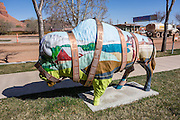 """Film Buff,"" a metal buffalo sculpture by artist Arlene Sibley, is installed at Kane County Information Center (address: 78 S 100 E, Kanab, Utah 84741, USA). Wrapping the buffalo is a film strip listing names of movies filmed in Kanab.  Kanab is home of the USA's first all-woman town council, elected in 1911, with Mary Woolley Chamberlain as mayor."