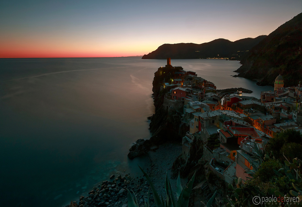 A comprehensive view of the medieval village of Vernazza, one of the five towns of the Italian Riviera in Liguria, Italy, alltogether known as Cinque Terre. Taken from a nice vantage point along the trail that from Vernazza goes to Corniglia, on a clear night at the beginning of April