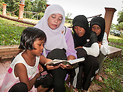 """Sept 27, 2009 -- BACHO, NARATHIWAT: SINA YUNUH and her daughter pray at a mass grave near the 300 Year Mosque in Bacho, Narathiwat, Thailand, for 22 Muslim men killed by Thai security forces in Oct. 2004. She said she believes her husband is buried here, but that his body was unidentifiable because of the mutilation. According to local community leaders, many of the men in the grave are unidentified because the bodies were mutilated beyond recognition before they were returned to their families.  Thailand's three southern most provinces; Yala, Pattani and Narathiwat are often called """"restive"""" and a decades long Muslim insurgency has gained traction recently. Nearly 4,000 people have been killed since 2004. The three southern provinces are under emergency control and there are more than 60,000 Thai military, police and paramilitary militia forces trying to keep the peace battling insurgents who favor car bombs and assassination.   Photo by Jack Kurtz / ZUMA Press"""