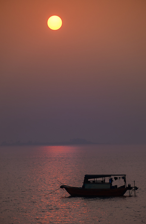 HA LONG BAY, VIETNAM - CIRCA SEPTEMBER 2014:  Fishing boat at sunrise during a foggy morning, in Halong Bay
