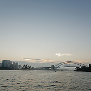 Sydney Bay during sunset seen from a ferry. In the far distance Syndey Harbour Bridge and The opera house.