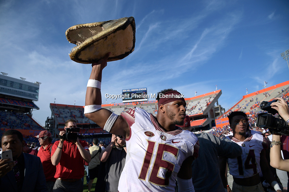 Florida State linebacker Jacob Pugh (16) hoists an alligator head on the field after an NCAA college football game against Florida Saturday, Nov. 25, 2017, in Gainesville, Fla. FSU won 38-22. (Photo by Phelan M. Ebenhack)