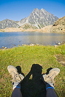 View of the photographers feet at the edge of Ingals Lake with Mount Stuart in the background, Washington Cascades, USA.
