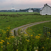 August 10, 2015, Green Bank, West Virginia: The Green Bank Telescope is seen from a farm in the quiet zone in rural West Virginia. The National Radio Astronomy Observatory in Green Bank, West Virginia, operates the world premiere astronomical telescope operating from centimeter to millimeter wavelengths.   The telescope sits near the heart of the United States National Radio Quiet Zone, a large area where all radio transmissions are limited to avoid emissions toward the GBT and the Sugar Grove Research Facility, West Virginia. The existence of the telescope within the Radio Quiet Zone allows for the detection of faint radio-frequency signals which otherwise would be eclipsed by man-made signals. The observatory borders the National Forest and is shielded from radio interference by the Allegheny Mountains. Photo by Evelyn Hockstein