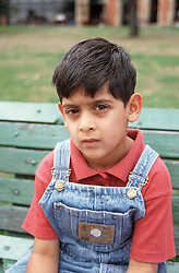 Portrait of young boy sitting on park bench looking serious,