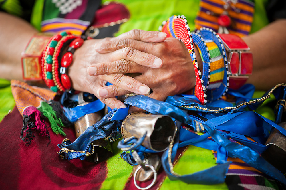 African American woman's hands wearing colorful traditional clothes and bracelets in Baltimore, Maryland. On her lap are bells and blue ribbons