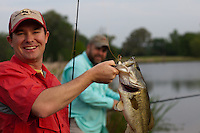 ANGLER SHOWING OFF A LARGEMOUTH BASS WHILE HIS FIREND LOOKS ON