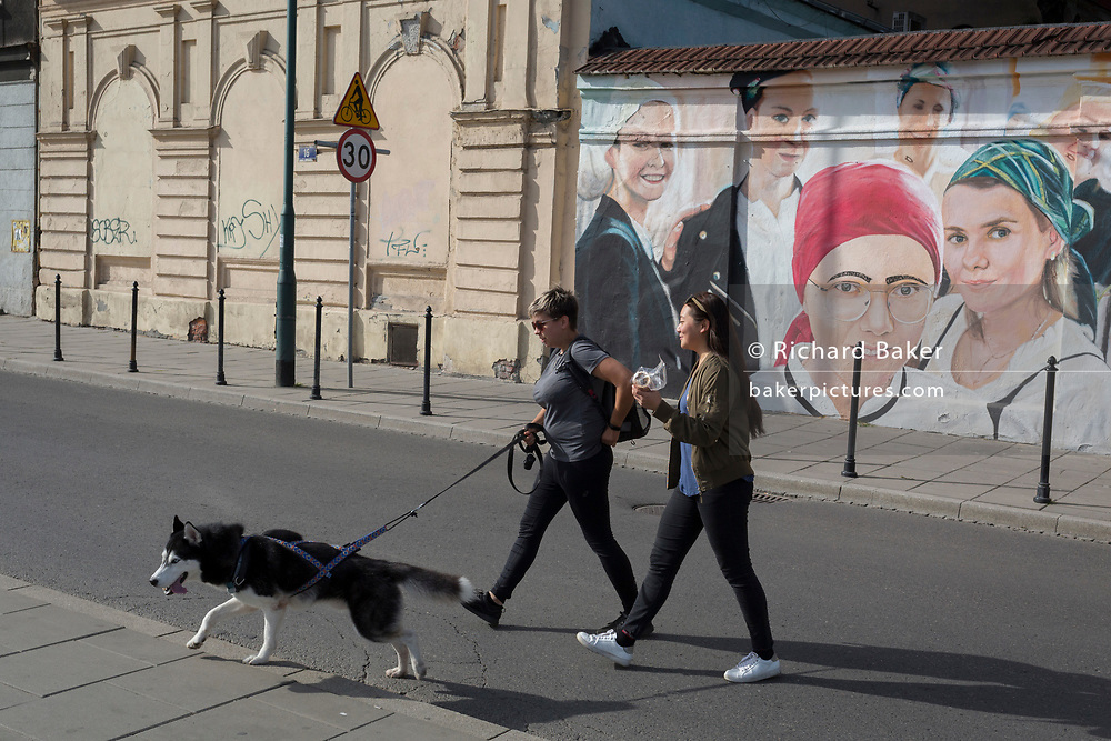 Two modern Polish women cross the road in front of a mural depicting a more traditional era in the Jewish Kazimierz district of Krakow, on 23rd September 2019, in Krakow, Malopolska, Poland.
