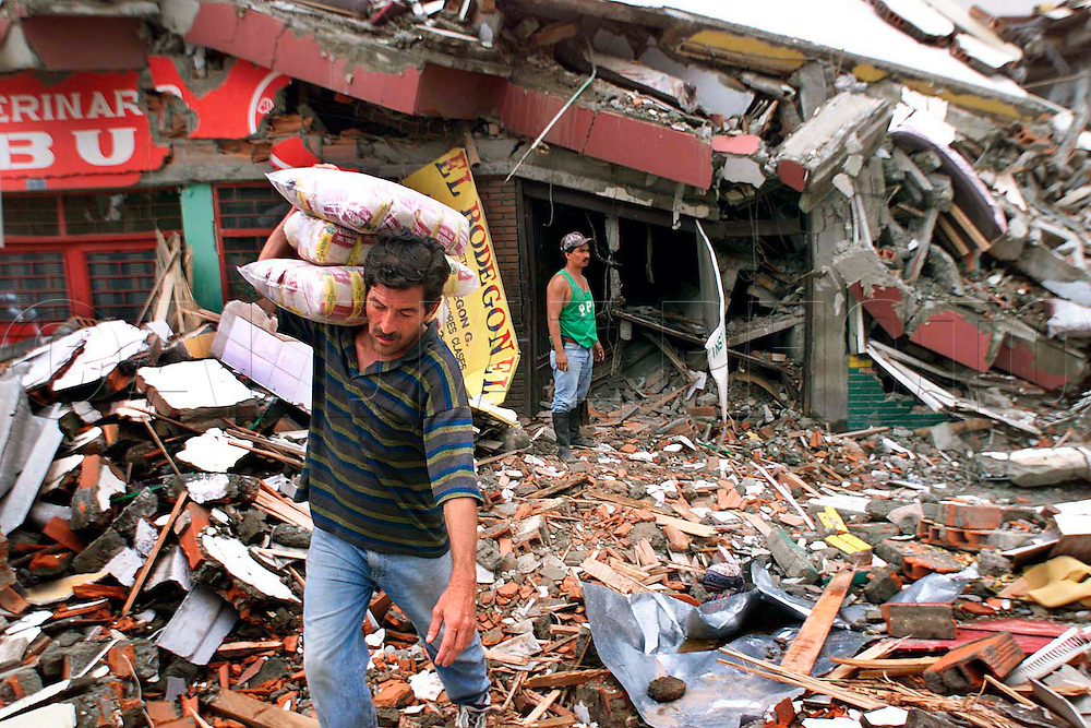 1/27/ 99 AL DIAZ/HERALD STAFF--Employee, Jose Jerman Tijaro recovers bags of rice from El Pasaje de la Papa a food store in Armenia struck hard by Monday's earthquake Colombia.