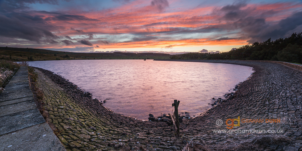 Sunset skies reflect in the rippled waters of Redmires lower Reservoir. A panoramic landscape captured in Sheffield, Peak District, South Yorkshire in September 2015.