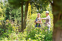 Male and female gardeners discussing over plants at plant nursery