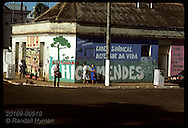 People walk by wall mural that protests Chico Mendes murder, on main street of Rio Branco. Brazil