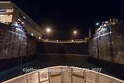 """Mules"" assists a shipping vessel to transit the Gatun Locks in the Panama Canal at night."