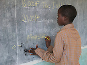 School pupils are being included in the methodolgy training at a primary school in Nyanza district, Rwanda. Here they are being encouraged to take part in the lesson by writing on the black board at the front of the classroom. This training was run by VSO education volunteers Melanie Pearson, Melissa Hipkins and Sarah Wragg.