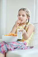 Little girl watching TV as she eats wheel shape snack pellets