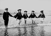 French coastal scene with children on a beach. Circa 1900