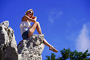 Blond female tourist admires the view while sitting on a rock on Aenos (Ainos) mountain on the Greek Island of Cephalonia, Ionian Sea, Greece with a blue sky background