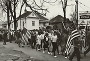 Participants, some carrying American flags, marching in the Civil Tights march from Selma to Montgomery, Alabama, USA, in 1965.  Photographer: Peter Pettus.
