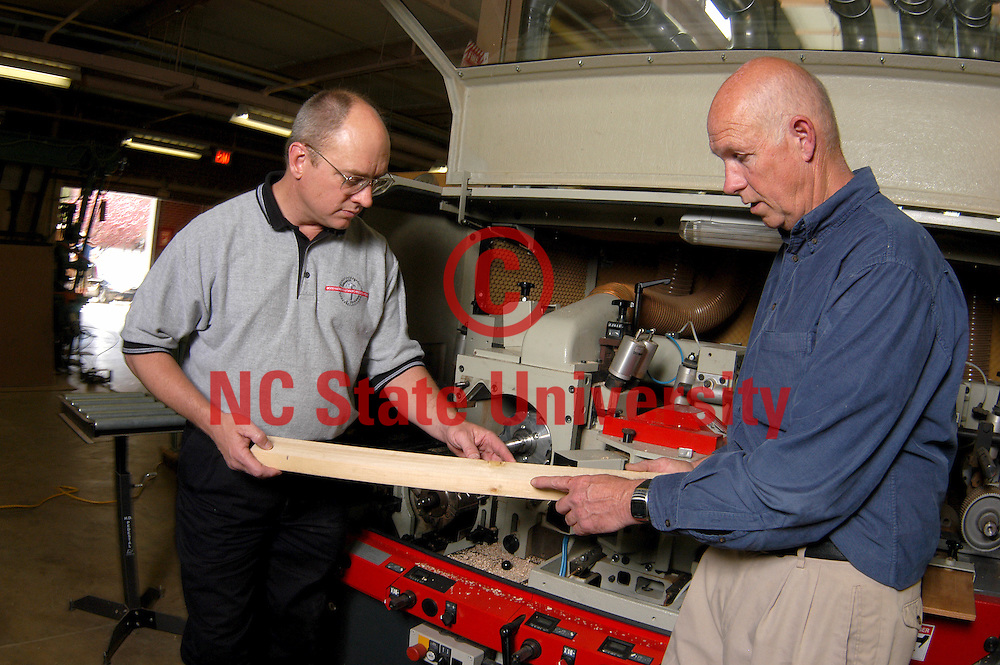 CNR's Wood Machining & Tooling Research Program (WMTRP) director Dr. Richard Lemaster (left) and WMTRP founder Dr. John Stewart and look over product manufactured in the woodworking shop off Dan Allen Drive.     PHOTO BY ROGER WINSTEAD
