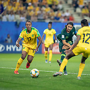 GRENOBLE, FRANCE June 18. Sam Kerr #20 of Australia completes her hat trick as she shoots past Sashana Campbell #12 of Jamaica to score her their goal of the game during the Jamaica V Australia, Group C match at the FIFA Women's World Cup at Stade des Alpes on June 18th 2019 in Grenoble, France. (Photo by Tim Clayton/Corbis via Getty Images)