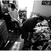 """Jenn Horne and Gabe Albanese are raising their daughter Jubilee in a collective house in Greenville N.C. Upon becoming pregnant the couple decided against moving out of the small room they share in the house into one of their own feeling it may """"isolate"""" the child. The house consists of between two and five college age roommates that are active in the community. Roommates tour in bands hold vegetarian dinner nights and strive to build a sense of community in a college town they describe as transient. Jenn Horne and Gabe dress their daughter Jubilee in the small room they share in Greenville N.C.   jfg"""