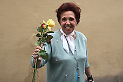 An old women with roses she received the international day of the Elderly (October 2, 2010).