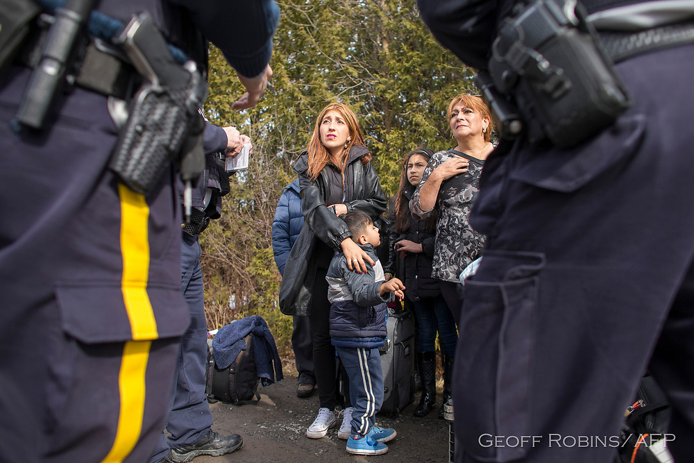 An extended family of 8 people from Colombia are detained by Royal Canadian Mounted Police officers after they illegally crossed the border near Hemmingford Quebec, February 25 2017.