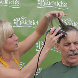 12 March 2009: A New Orleans Hornets Honeybee NBA dancer shaves the head of a participant during the annual St. Baldrick's charity fund raiser held at Parasol's Bar in the Irish Channel of New Orleans, Louisiana.
